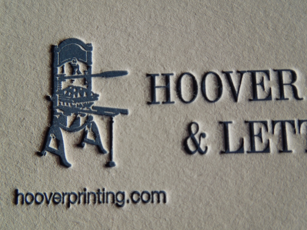 The text and image of a printing press are deep in this business card.