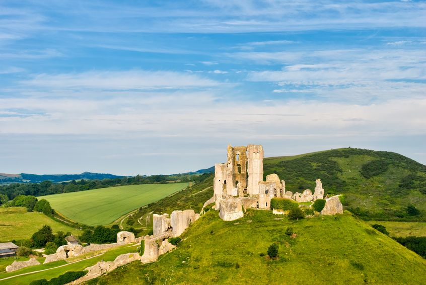 The ruins of Corfe Castle, Dorset, England. Castle is on a green hill with blue sky.