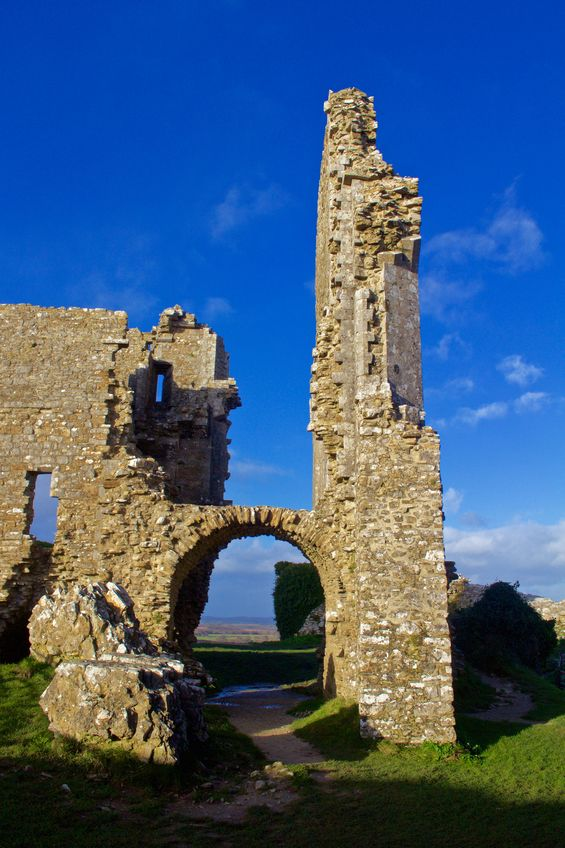 Ruins around an archway at Corfe Castle, Dorset, England. Tall ruin against a brilliant blue sky.